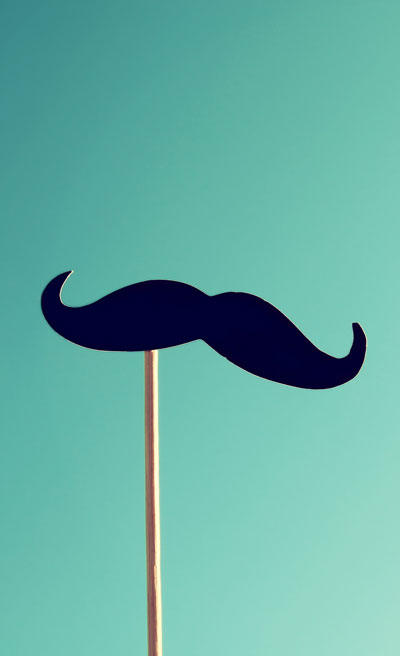 Mustache on stick against the blue sky