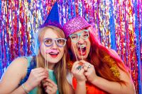 Two girls having a great time in a birthday party photo booth