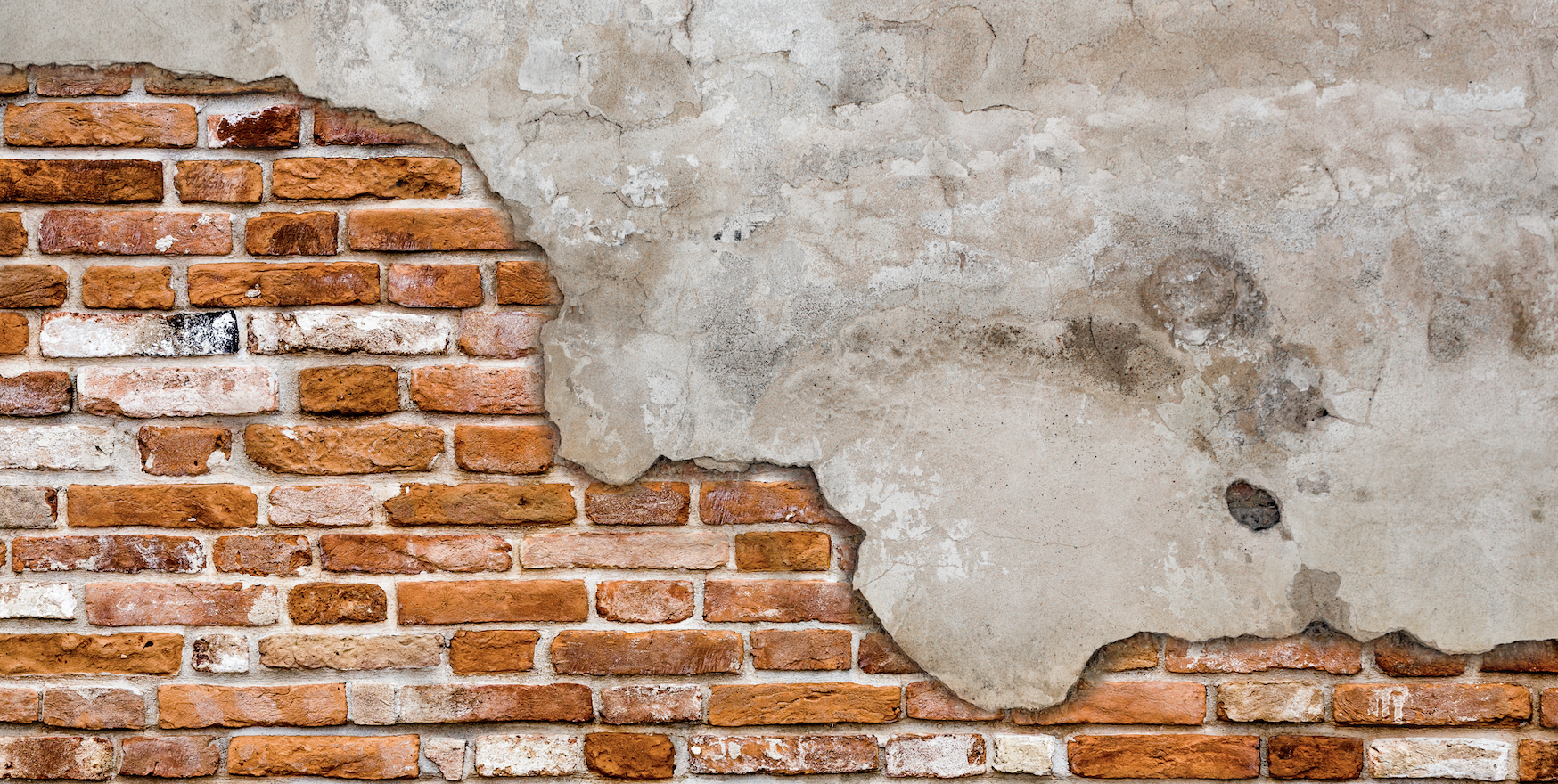 An exposed brick wall on an old building.