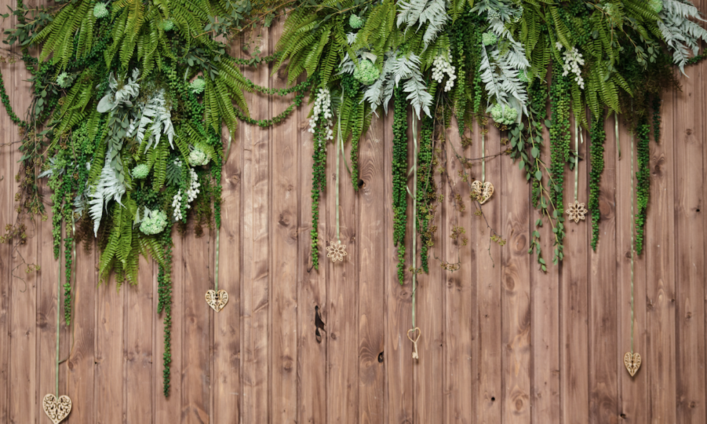 A leaf wall on a wooden background perfect for a party.